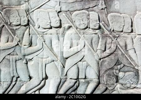 Ancient Khmer bas relief carving showing the Khmer army going into battle. Some of their colleagues are lying drunk on the floor. Outer wall of Bayon - Stock Photo