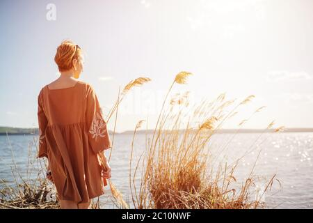 Woman with short hair standing on a lake shore, looking afar Stock Photo