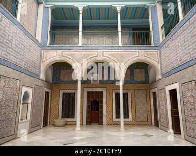 Ornate tiled courtyard of a restored Ottoman palace in the heart of the medina of Tunis with filigreed arches, marble floors and varied tile designs.
