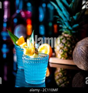 Blue curaçao cocktail garnished with pineapple  and orange pieces served in a bar. - Stock Photo