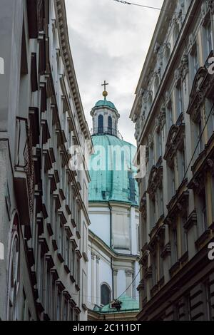 The dome of St. Peter's Church ( Peterskirche )  appears between the facades of buildings with classical Viennese architecture, Vienna, Austria. - Stock Photo