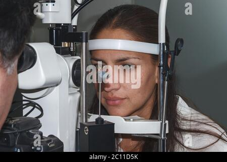 Beautiful young woman having eye test at the optometrist - Stock Photo