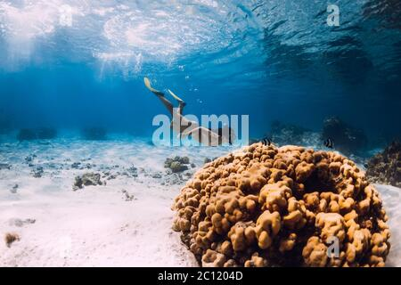 Woman freediver glides with yellow fins over sandy sea. - Stock Photo