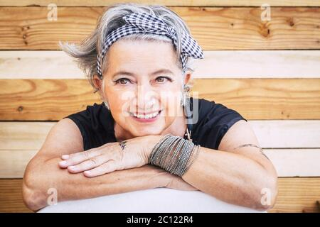 Portrait of cheerful caucasian senior happy woman with wood background - alternative and young old female smile and enjoy - tatooed skin for diversity