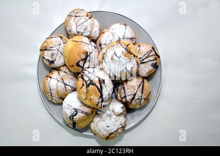 Homemade chocolate crinkles cookies powdered sugar on white backgrounds . Top view . Homemade chocolate crinkles on a white square plate . - Stock Photo