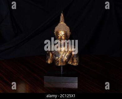 Still life of Bronze Thai Buddha in gold leaf finish. Beautiful ornamental Interior display Bronze sculpture - Stock Photo