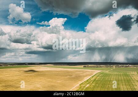 Aerial View. Amazing Natural Dramatic Sky With Rain Clouds Above Countryside Rural Field Landscape In Spring Summer Cloudy Day. Scenic Sky With Fluffy