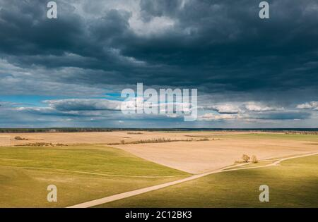 Aerial View. Amazing Natural Dramatic Sky With Rain Clouds Above Countryside Rural Field Landscape In Spring Day. Scenic Sky With Fluffy Clouds On