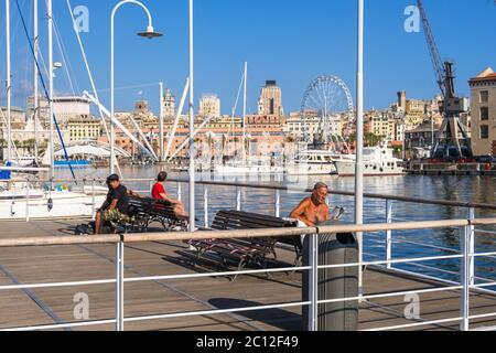 Genoa, Italy - August 18, 2019: People relax on benches on the floating pier of the Porto Antico di Genova or Old Port of Genoa, Liguria region, Italy - Stock Photo