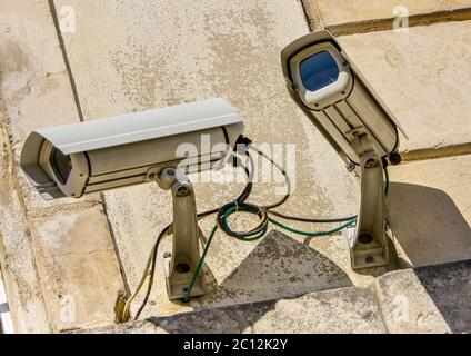 two security CCTV cameras or surveillance system in office building - Stock Photo