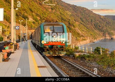 A train travels into the Monterosso al Mare train station on the Cinque Terre coast of Italy as travelers sit and enjoy a warm day in early autumn - Stock Photo