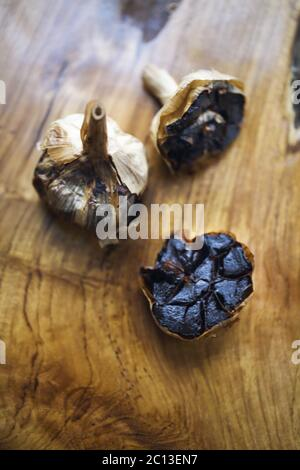 Black garlic bulbs and cloves on wooden background