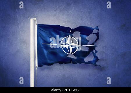 Torn flag of the North Atlantic Treaty Organization NATO against grunge background - Stock Photo