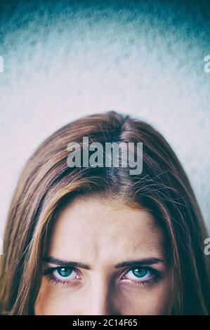 half face of a young woman staring with an intense gaze