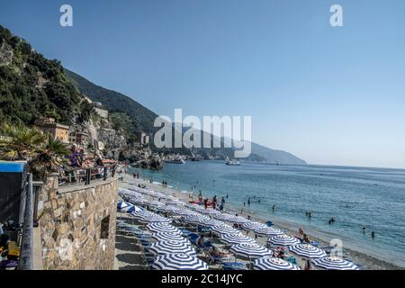 vacation beach with colorful rainbow chaise lounge chairs and umbrellas. resort beach. Monterosso al Mare, Cinque Terre, Italy - Stock Photo