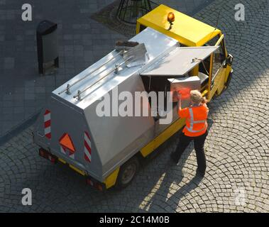 Small garbage truck with female worker in shopping street. She throws waste from the market in a truck on behalf of a municipality in the Netherlands - Stock Photo