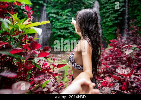 Couple in love man and woman holding hands, lovers at the waterfall, rear view.traveling together outdoor romantic vacations honeymoon lifestyle