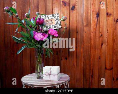 Pink flowers peonies in a vase on a wooden background with a small white gift and a happy birthday card. The photo was taken with natural daylight. - Stock Photo