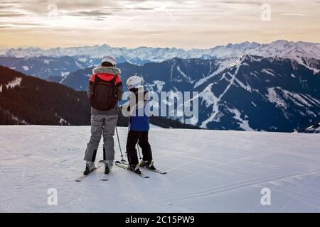 Family, skiing in winter ski resort on a sunny day, enjoying scenery landscape - Stock Photo