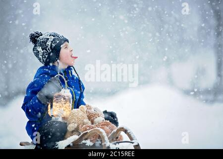 Cute boy playing with teddy bear in the snow, winter time. Little toddler playing with toys on a snowy day