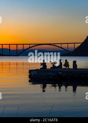 Family together dusk evening free time fishing bridge mainland to island Krk in background silhouettes silhouetting silhouette pretty picturesque - Stock Photo