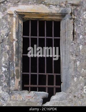 A window with a rusty metal grille of a historic ruined building .Background or texture - Stock Photo