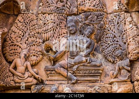 Ancient Khmer bas relief carving showing the Hindu gods Shiva and Uma sitting on Mount Kailas. Banteay Srei Temple, Angkor, Cambodia. - Stock Photo