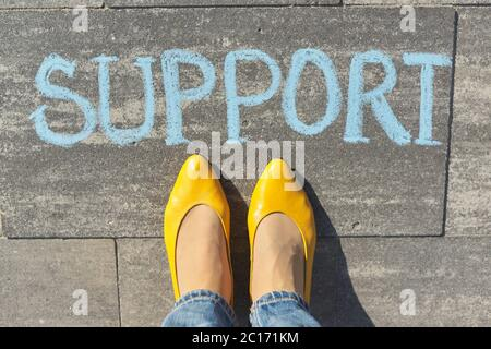 Support concept, top view on woman legs and text written in chalk on gray sidewalk - Stock Photo