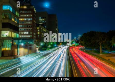Busy Boston street view featuring car light trails on the foreground - Stock Photo