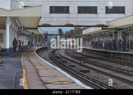 South West Trains class 444 electric train arriving at the crowded platforms at Surbiton railway station in the morning rush hour - Stock Photo
