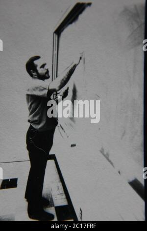 Fine 70s vintage black and white extreme photography of a teacher standing at the chalkboard and writing on it.