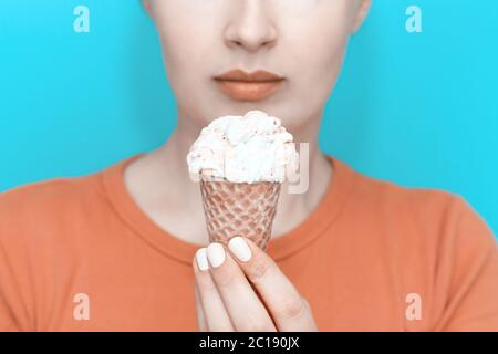 Young beautiful girl holds ice cream cone on blue background, 19th World Ice Cream Day - Stock Photo