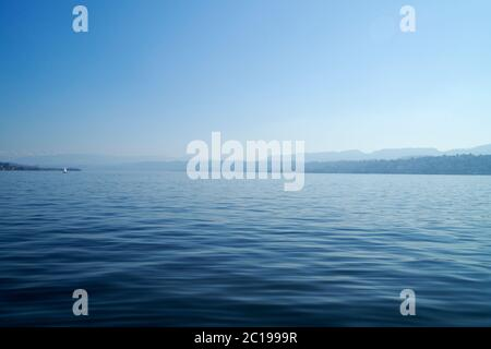 Stunning view over Lake Zurich in Switzerland with the mountains in the background in clear day with blue sky - Stock Photo