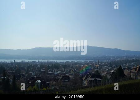 Stunning view over the city of Zurich in Switzerland with the mountains in the background in clear day with blue sky - Stock Photo