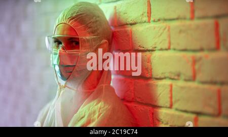 Doctor in protective suit on background of brick wall in red zone. - Stock Photo