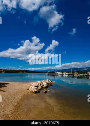 Pretty sand beach scenery in Soline on island Krk Croatia bunch of rocks protruding from sea surface immersed Summer clouds reflected in water - Stock Photo