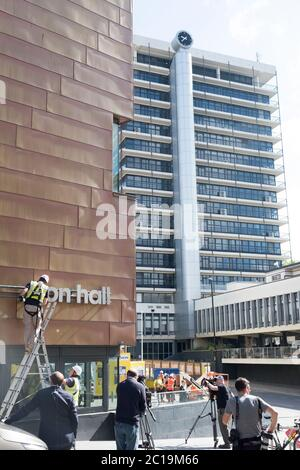Bristol, UK. 15th June, 2019. The sign for the Colston Hall is removed today. Edward Colston has been a contentious figure in Bristol's history, in 2018 the board of the Colston Hall decided Colston was a toxic brand and decided to change the name of this prestigious venue. The Black Lives Matter protest where the statue of Colston was thrown in the harbour has energised the removal of his name from the hall. Colston Tower where the name was removed last week in the background. Credit: Mr Standfast/Alamy Live News - Stock Photo