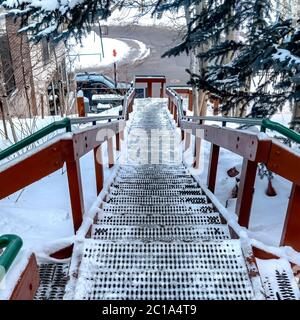 Square frame Stairway and road on snow covered hill amid houses and coniferous trees - Stock Photo