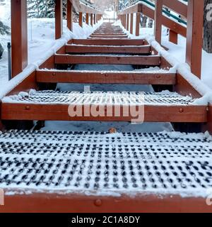 Square Focus on grate metal treads of outdoor stairs against snowy hill in winter - Stock Photo