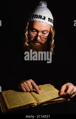 Hasidic jew reading Torah. Religious orthodox jew with sidelocks and red beard in white bale praying in the dark. Low key photo - Stock Photo