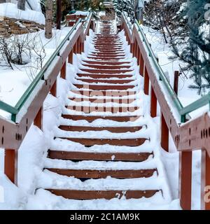 Square frame Focus on stairway that goes up a snowy hill with residential homes in winter - Stock Photo