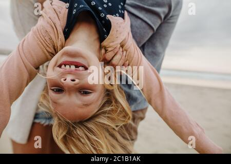Girl being carried by her parents on the beach. Girl enjoying on a summer vacation with her parents. - Stock Photo