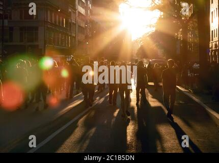 Crowd of people walking down the street into the bright light of sunset in New York City NYC - Stock Photo