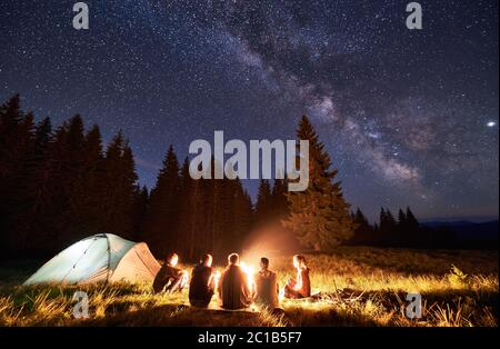 Night summer camping in the mountains, spruce forest on background, sky with stars and milky way. Back view group of five tourists having a rest together around campfire, enjoying fresh air near tent.