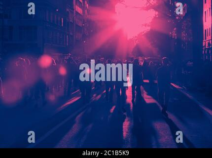 Crowd of people walking down the street into the bright light of sunset in New York City with pink and blue color effect - Stock Photo