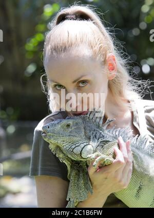 The young woman kisses an iguana, holds her on hands - Stock Photo