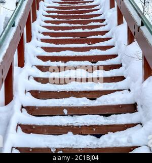 Square Focus on stairway that goes up a snowy hill with residential homes in winter - Stock Photo