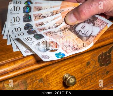 Close POV shot of a hand holding six, new polymer ten pound sterling notes, spread out over an ornate wooden drawer unit. - Stock Photo