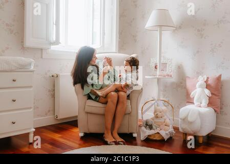 Pregnant young woman plays with her girl sitting in the room - Stock Photo