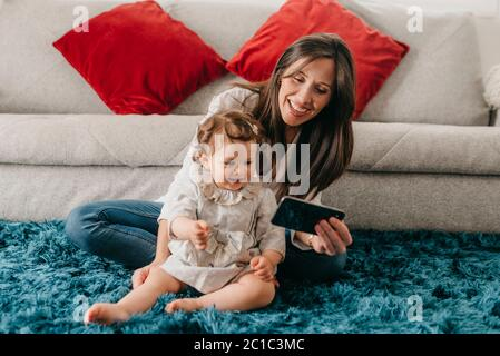 young pretty mother plays with her daughter on the living room floor with the phone - Stock Photo